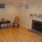 Renovated basement including insulation, finished drywall, laminate flooring, gas fireplace, and updated colonial fireplace mantle
