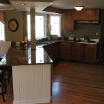 Remodeled kitchen with granite countertops, cherry cabinets, stainless appliances, and wall-mounted flatscreen TV