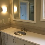 Remodeled master bathroom with porcelain wall and floor tile, glass accent tiles, Kohler fixtures, Corian vanity top, and updated vanity cabinets