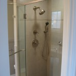 Remodeled shower with porcelain wall and floor tile, glass accent tiles, Kohler Mastershower fixtures, and custom glass door
