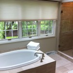 Remodeled and updated master bathroom with porcelain tile throughout, MTI soaking tub, and Grohe tub faucets