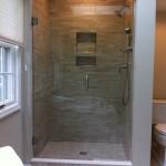 Remodeled and updated shower with porcelain mosaic tile, recessed niche, Kohler Mastershower fixtures, and custom frameless shower door