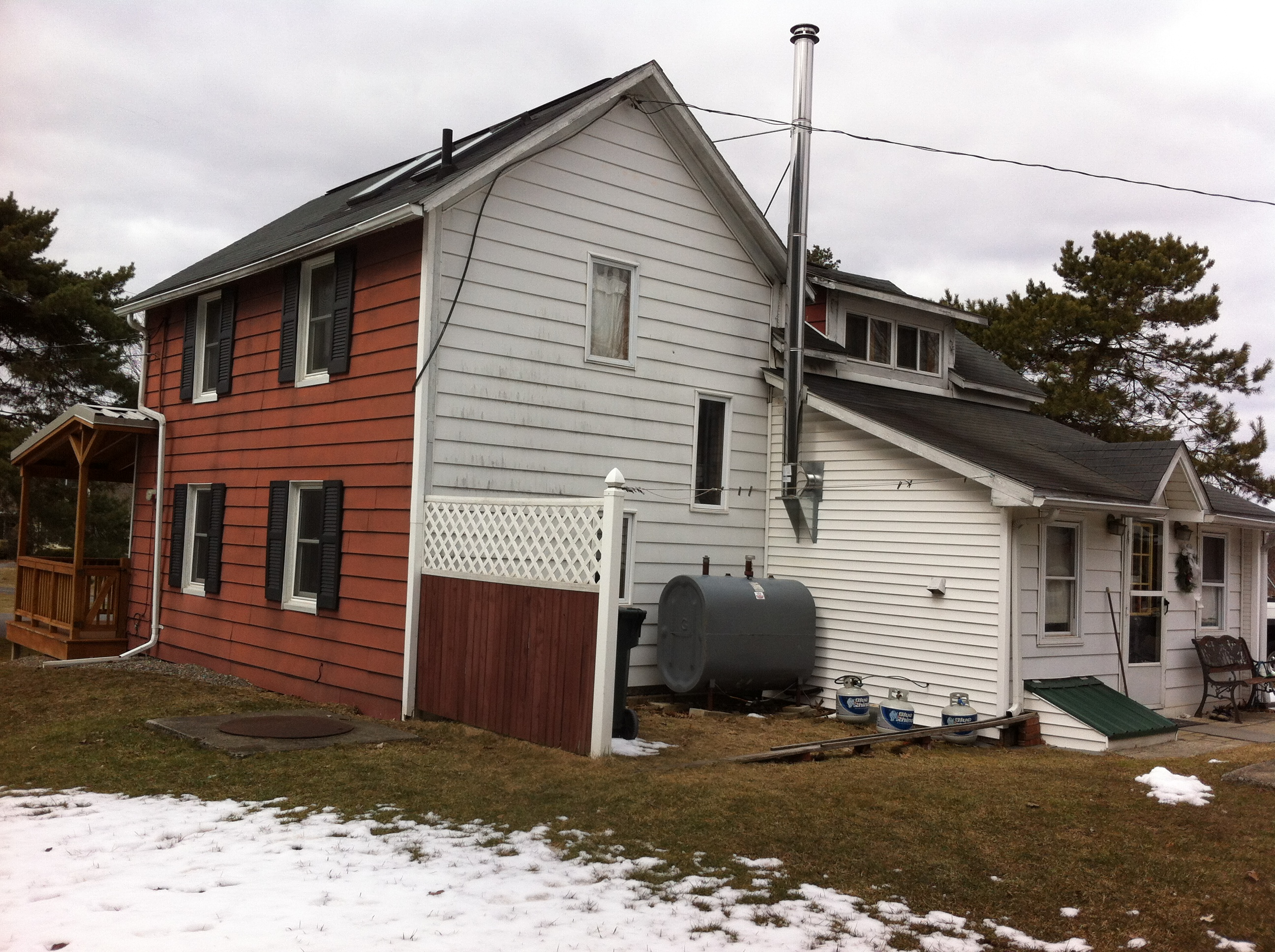 Old farmhouse with aluminum and vinyl siding, ready for excavation for addition foundation