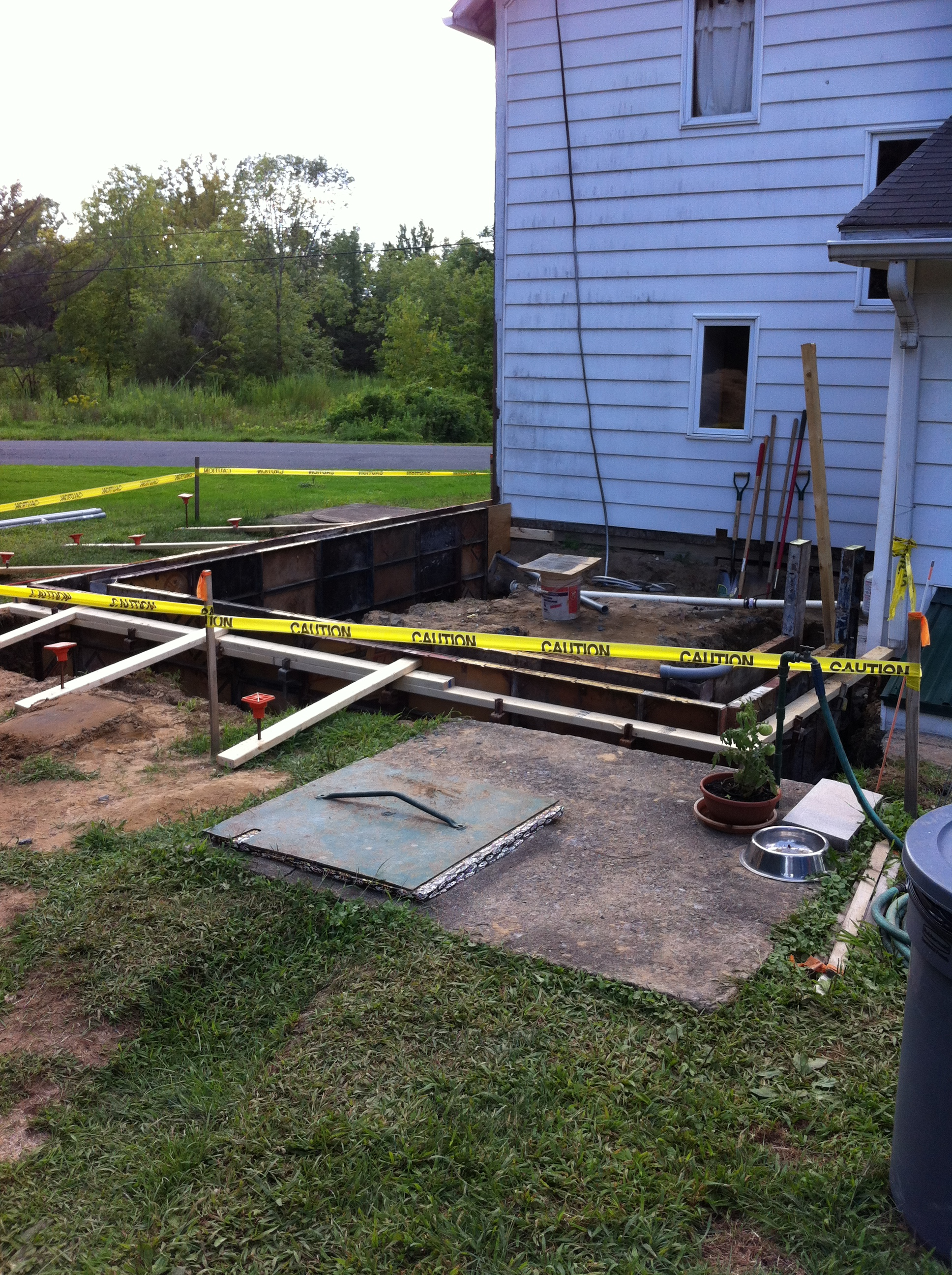 Excavated site with concrete footings (below grade) and formwork for foundation frostwalls