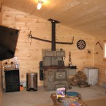 """Man Cave"" inside newly-constructed barn, with flatscreen TV, beverage cooler, and original wood stove to farmhouse kitchen"