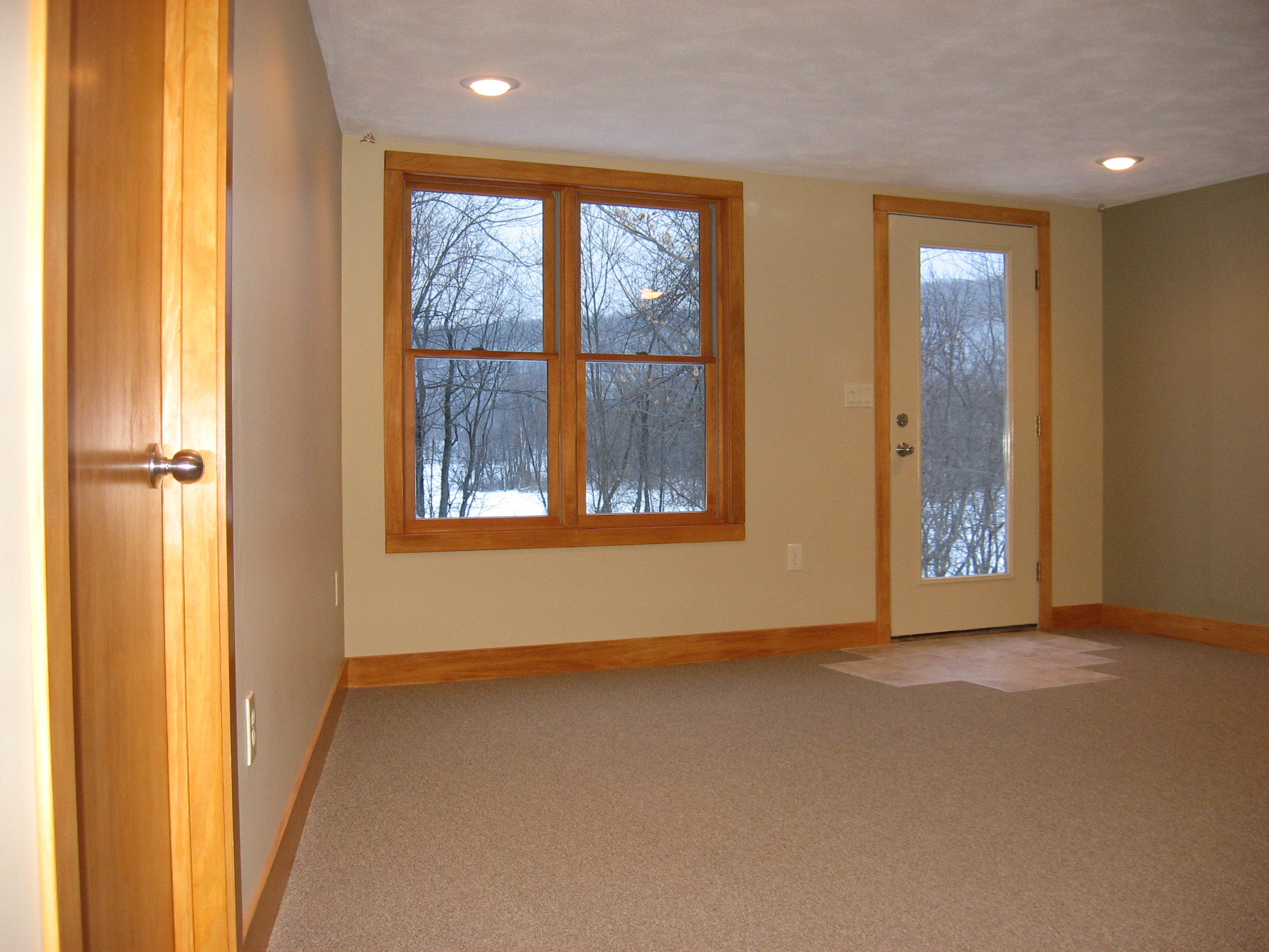 Finished basement renovation with stained birch doors, poplar baseboard and casing, recessed lights, and staggered ceramic tile at full-lite entry door