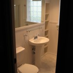Basement bathroom with ceramic tile, built in shelving, chrome faucets, beadboard paneling, and glass block window