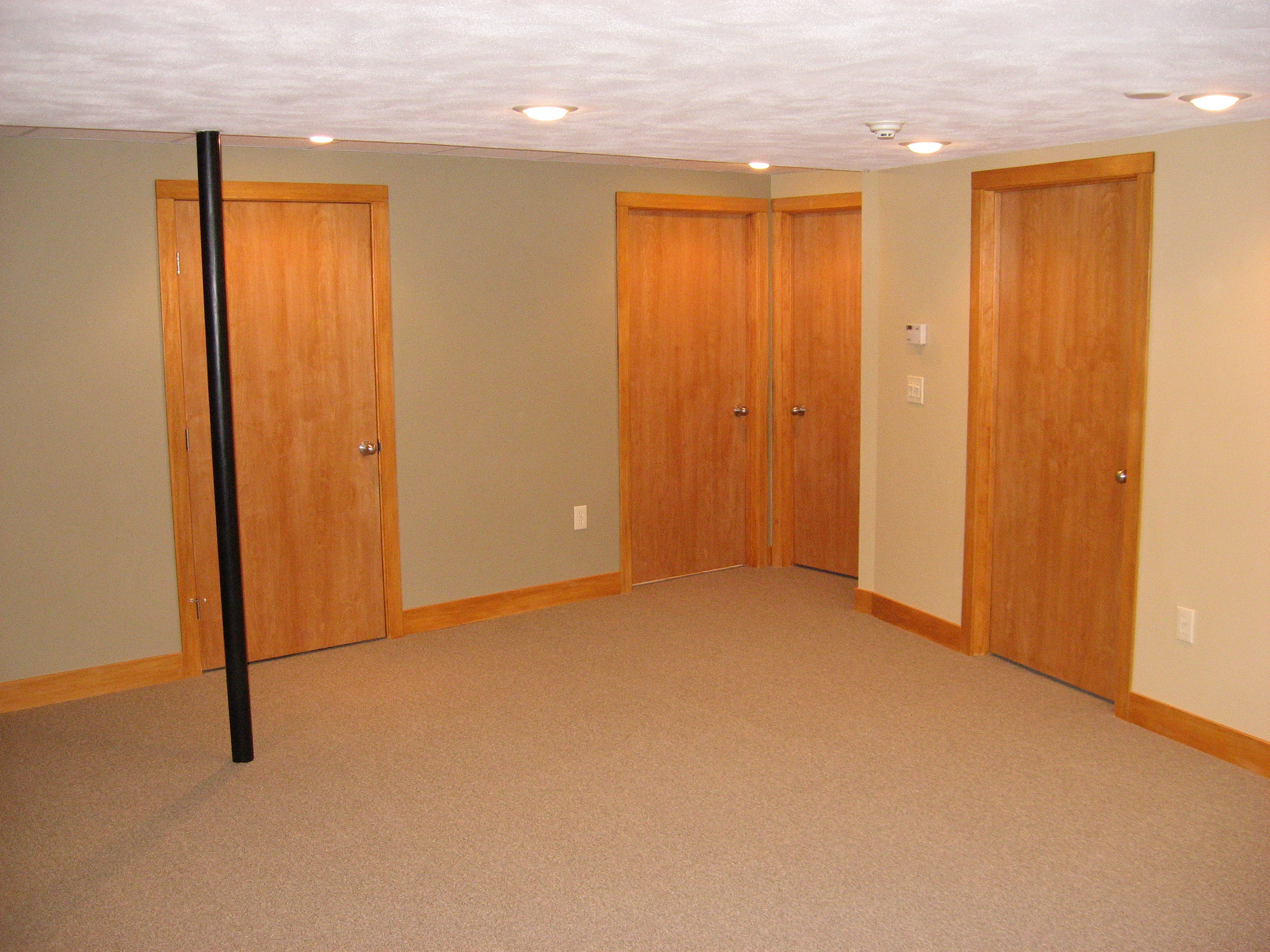 Finished basement renovation with stained birch doors, poplar baseboard and casing, and recessed lighting