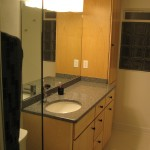 Master bathroom with maple cabinetry, Corian vanity top, and glass block window