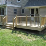 Deck with premium pressure-treated deckboards and colonial rail system