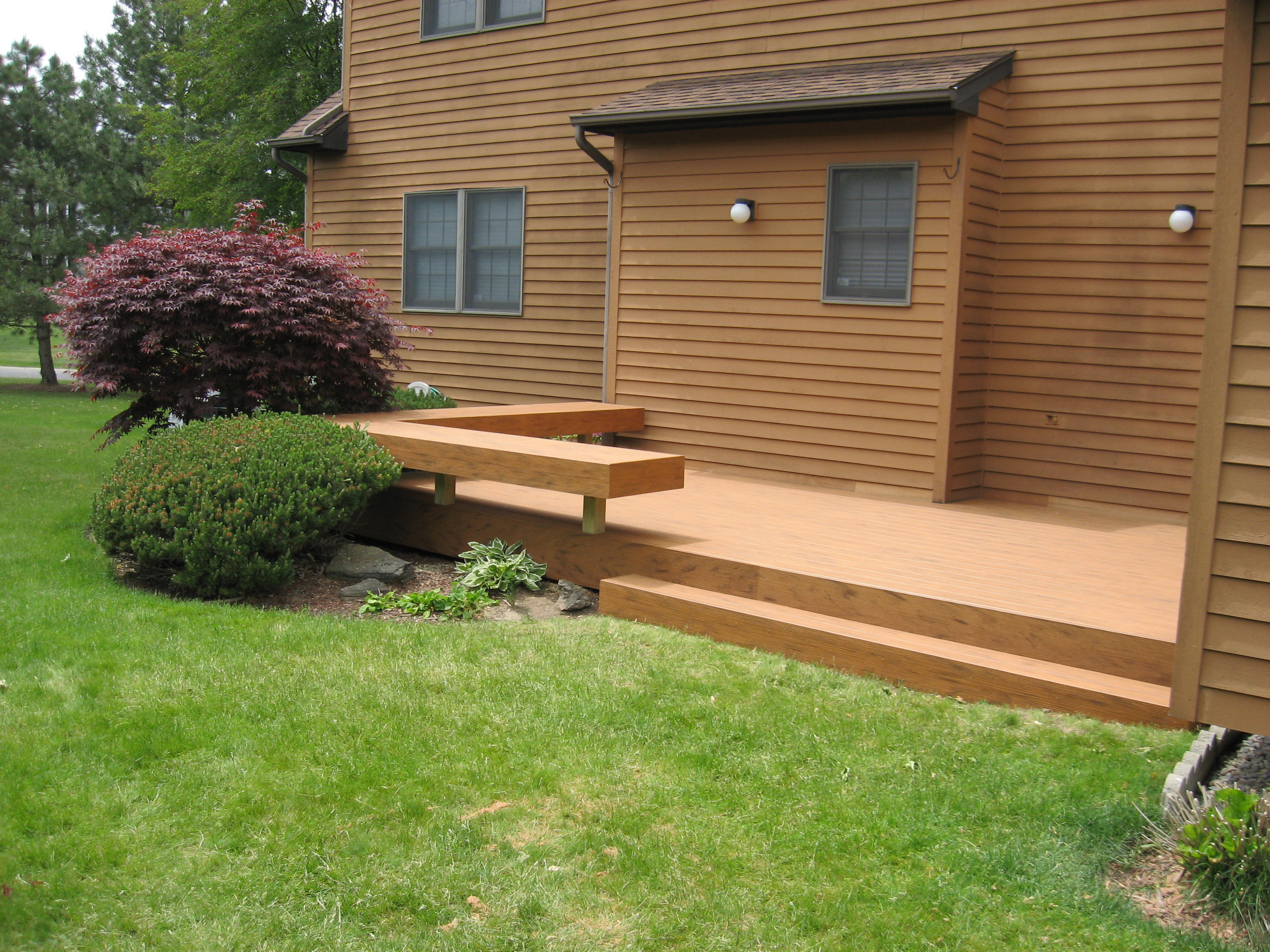 Ground deck with TimberTech deckboards, trimboards, and matching bench seating